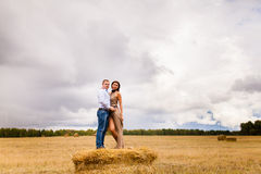 Ερωτευμένοι νέοι ζεύγους που στηρίζονται στη θυμωνιά χόρτου Στοκ φωτογραφία με δικαίωμα ελεύθερης χρήσης