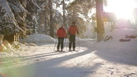 Ερωτευμένοι περίπατοι ζεύγους να κάνει σκι στο χιονοδρομικό κέντρο στο τελευταίο φως του ήλιου φιλμ μικρού μήκους