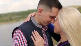Ερωτευμένο αγκάλιασμα ζεύγους που στέκεται κοντά στη λίμνη απόθεμα βίντεο