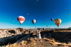 Ερωτευμένο αγκάλιασμα ζεύγους στα βουνά μεταξύ των μπαλονιών στοκ εικόνα με δικαίωμα ελεύθερης χρήσης
