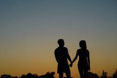 Ερωτευμένο ζεύγος που περπατά στο υπόβαθρο ηλιοβασιλέματος Στοκ Εικόνες