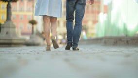 Ερωτευμένο περπάτημα ζεύγους στο πεζοδρόμιο στη μεσημβρία Ο καιρός έχει ήλιο και θερμότητα διασκέδαση ζευγών που έχ& απόθεμα βίντεο