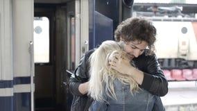 Ερωτευμένο ρητό ζεύγους αντίο και φίλημα στην πλατφόρμα σταθμών τρένου τη βροχερή ημέρα απόθεμα βίντεο
