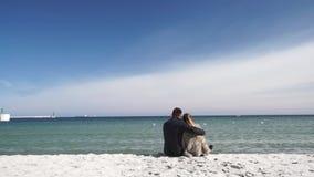Ερωτευμένο τρέχοντας παιχνίδι ζεύγους στην παραλία στην κρύα ημέρα απόθεμα βίντεο