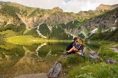 Ερωτευμένο φίλημα ζεύγους μπροστά από τη λίμνη βουνών από τη Βαυαρία, Γερμανία Όμορφο ζεύγος στη φύση Στοκ Εικόνα