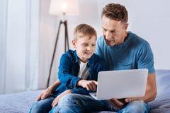 Ερωτεύσιμο αγόρι και τα κινούμενα σχέδια προσοχής πατέρων του στο κρεβάτι Στοκ φωτογραφία με δικαίωμα ελεύθερης χρήσης