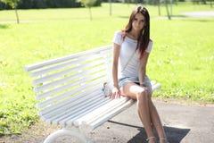 Ερωτικό κορίτσι με τη μίνι φούστα στην πράσινη χλόη Στοκ Φωτογραφίες