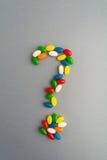 Ερώτηση σημαδιών Jellybean πέρα από το γκρίζο υπόβαθρο στοκ φωτογραφίες