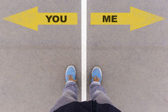 Εσείς ή εγώ βέλη κειμένων στο έδαφος, τα πόδια και τα παπούτσια ασφάλτου στο πάτωμα Στοκ Φωτογραφίες