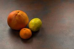 Εσπεριδοειδή: πορτοκάλι, λεμόνι, tangerine στο σκοτεινό υπόβαθρο πετρών στοκ φωτογραφία