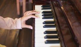 Εστίαση ένα θηλυκό χέρι που παίζει το ξύλινο πιάνο και το δαχτυλίδι της στοκ φωτογραφία