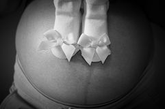 Εστίαση στις νεογέννητες κάλτσες κοριτσιών με την κορδέλλα στο στομάχι της εγκύου γυναίκας Στοκ Εικόνες
