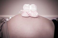Εστίαση στις νεογέννητες κάλτσες κοριτσιών με την κορδέλλα στο στομάχι της εγκύου γυναίκας Στοκ φωτογραφία με δικαίωμα ελεύθερης χρήσης