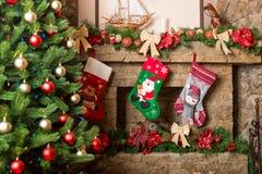 Εστία που διακοσμείται πέτρινη με τις γυναικείες κάλτσες Χριστουγέννων Στοκ Εικόνες