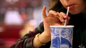 Εστιατόριο γρήγορου φαγητού: κορίτσι που πίνει το κρύο ποτό με το άχυρο φιλμ μικρού μήκους