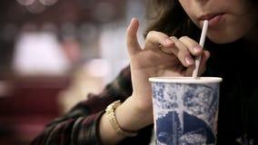 Εστιατόριο γρήγορου φαγητού: κορίτσι που πίνει το κρύο ποτό με το άχυρο απόθεμα βίντεο