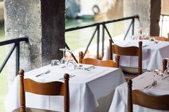 Εστιατόριο στο κανάλι Βενετία Πίνακας που θέτει για ένα καλό γεύμα Γυαλιά που τίθενται κενά στον καφέ εσωτερικό μέρος πετσέτες Στοκ Εικόνα