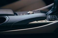 Εσωτερικά σύγχρονα στοιχεία αυτοκινήτων, κινηματογράφηση σε πρώτο πλάνο handbrake και ζώνη ασφαλείας στοκ εικόνες