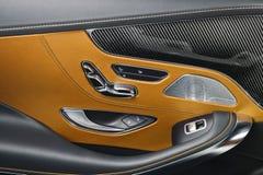 Εσωτερικές λεπτομέρειες δέρματος και άνθρακα αυτοκινήτων καφετιές της λαβής πορτών με τους ελέγχους και τις ρυθμίσεις καθισμάτων  Στοκ εικόνες με δικαίωμα ελεύθερης χρήσης