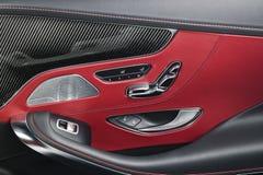 Εσωτερικές λεπτομέρειες δέρματος και άνθρακα αυτοκινήτων κόκκινες της λαβής πορτών με τους ελέγχους και τις ρυθμίσεις καθισμάτων  Στοκ Εικόνα