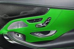 Εσωτερικές λεπτομέρειες δέρματος και άνθρακα αυτοκινήτων πράσινες της λαβής πορτών με τους ελέγχους και τις ρυθμίσεις καθισμάτων  Στοκ Εικόνες