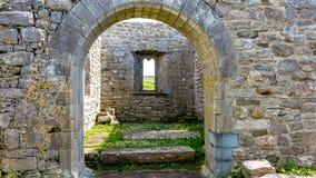 Εσωτερική άποψη των καταστροφών της μεσαιωνικής εκκλησίας Killilagh μέσω μιας πύλης πετρών στο χωριό Doolin στοκ φωτογραφία