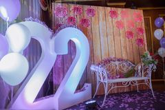 Εσωτερική διακόσμηση για γενέθλια Άσπρος πάγκος σιδήρου πορφύρα λουλουδιών πορφύρα πετάλων λουλου&d 22 χρονών γράφοντας Εορταστικ Στοκ Φωτογραφία