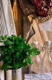 Εσωτερικός, ξύλινος τέμνων πίνακας κουζινών της Προβηγκίας αγροτικός, εργαλεία, μπουκάλια γυαλιού, φρέσκα χορτάρια, πετσέτα λινού Στοκ Φωτογραφία