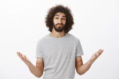 Εσωτερικός πυροβολισμός του ανίδεου ταραγμένου ισπανικού φίλου με το afro hairstyle και την αρσενική γενειάδα, που αυξάνει τους φ στοκ εικόνες