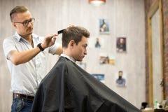 Εσωτερικός πυροβολισμός της διαδικασίας εργασίας στο barbershop Στοκ Εικόνες