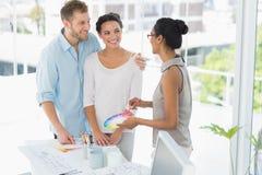 Εσωτερικός σχεδιαστής που παρουσιάζει ρόδα χρώματος στους ευτυχείς νέους πελάτες Στοκ φωτογραφία με δικαίωμα ελεύθερης χρήσης