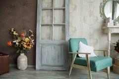 Εσωτερικό αναδρομικό δωμάτιο με μια πολυθρόνα, τα λουλούδια, την πόρτα και τον καθρέφτη Στοκ φωτογραφία με δικαίωμα ελεύθερης χρήσης