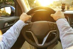 Εσωτερικό αυτοκινήτων με την αρσενική συνεδρίαση οδηγών πίσω από τη ρόδα, μαλακό φως ηλιοβασιλέματος Πολυτελές ταμπλό και ηλεκτρο στοκ φωτογραφία με δικαίωμα ελεύθερης χρήσης