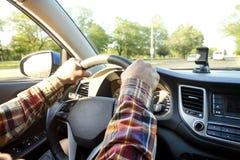Εσωτερικό αυτοκινήτων με την αρσενική συνεδρίαση οδηγών πίσω από τη ρόδα, μαλακό φως ηλιοβασιλέματος Πολυτελές ταμπλό και ηλεκτρο στοκ φωτογραφίες
