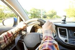 Εσωτερικό αυτοκινήτων με την αρσενική συνεδρίαση οδηγών πίσω από τη ρόδα, μαλακό φως ηλιοβασιλέματος Πολυτελές ταμπλό και ηλεκτρο στοκ εικόνα με δικαίωμα ελεύθερης χρήσης