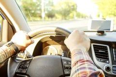 Εσωτερικό αυτοκινήτων με την αρσενική συνεδρίαση οδηγών πίσω από τη ρόδα, μαλακό φως ηλιοβασιλέματος Πολυτελές ταμπλό και ηλεκτρο στοκ εικόνες με δικαίωμα ελεύθερης χρήσης