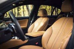 Εσωτερικό αυτοκινήτων: Μπεζ καθίσματα αυτοκινήτων δέρματος μπροστινά στοκ φωτογραφία