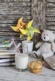 Εσωτερικό γραφείο εργασίας παιδιών με τα βιβλία, τα σημειωματάρια, τα σημειωματάρια, το ποτήρι του γάλακτος και ένα κουλούρι Στοκ φωτογραφία με δικαίωμα ελεύθερης χρήσης