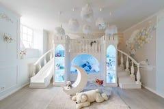εσωτερικό ενός ευρύχωρου δωματίου παιδιών ` s διακοσμητικό κάστρο με το κρεβάτι μέσα, τη φωτογραφική διαφάνεια παιχνιδιών και τα  Στοκ φωτογραφία με δικαίωμα ελεύθερης χρήσης