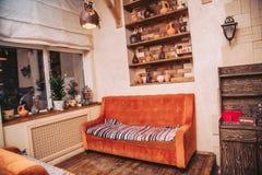 Εσωτερικό ενός χαριτωμένου καφέ Καναπές και ξύλινα ράφια με τις κανάτες αργίλου Στοκ Εικόνες