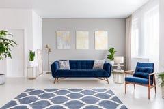 Εσωτερικό καθιστικών ανοιχτού χώρου με έναν μπλε ναυτικό καναπέ και μια πολυθρόνα Κουβέρτα στο πάτωμα και γραφικές διακοσμήσεις σ στοκ φωτογραφίες