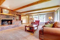 Εσωτερικό καθιστικών με την εστία τούβλου, τις ξύλινες ακτίνες και το κόκκινο. Στοκ εικόνες με δικαίωμα ελεύθερης χρήσης