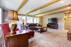 Εσωτερικό καθιστικών με την εστία τούβλου, τις ξύλινες ακτίνες και το κόκκινο. Στοκ Εικόνα