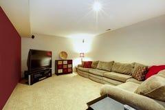 Εσωτερικό καθιστικών με τον μπεζ καναπέ, το πάτωμα ταπήτων και τον κόκκινο τοίχο Στοκ Εικόνες