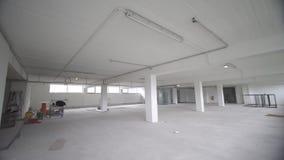 Εσωτερικό κενό ελαφρύ δωμάτιο γραφείων με την άσπρη ταπετσαρία χωρίς έπιπλα σε μια νέα ανακαίνιση οικοδόμησης ή κάτω φιλμ μικρού μήκους