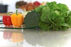 Εσωτερικό κουζινών Πολλά λαχανικά και άλλο γεύμα στον πίνακα γυαλιού είναι έτοιμα για μαγειρευμένος σύντομα Στοκ Φωτογραφίες