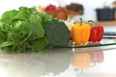 Εσωτερικό κουζινών Πολλά λαχανικά και άλλο γεύμα στον πίνακα γυαλιού είναι έτοιμα για μαγειρευμένος σύντομα Στοκ Εικόνες