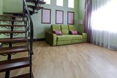 Εσωτερικό με μια μεταλλική μαύρη σκάλα με τα ξύλινα βήματα και έναν πράσινο καναπέ στο καθιστικό στοκ εικόνες