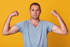 Εσωτερικό στούντιο που πυροβολείται του όμορφου αθλητικού νεαρού άνδρα που παρουσιάζει μυς, αυξάνοντας τα όπλα του, εξετάζοντας ά στοκ εικόνες