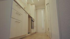 Εσωτερικό σχέδιο της καθαρής σύγχρονης άσπρης και μαύρης κουζίνας με τον εξοπλισμό ανοξείδωτου απόθεμα βίντεο